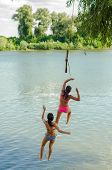 Two Teenage Girls Jumping Into The River