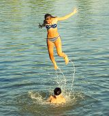 Teenage Girl Jumping Into The River From Boys Shoulders