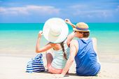 back view of couple in straw hats sitting at tropical beach