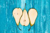 Juicy pear slices on blue wood background