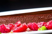 ..dark Chocolate Cake. Slice Of Chocolate Layer Cake With Red Berries And Chocolate Sauce Macro.