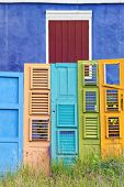 Collection of colorful old wooden doors in front of blue house with red shutters