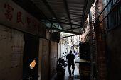 TAIPEI, TAIWAN - November 16th : Someone walk through a narrow alley near Longshan Temple, Taipei, Taiwan on November 16th, 2014.
