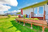 Countryside House Exterior With Walkout Deck And Small Patio Area.