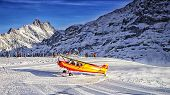 Yellow Airplane Landing To  Alpine Resort In Swiss Alps In Winter2