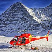 Red Helicopter Landed Near Alpine Peak Near Jungfrau Mountain