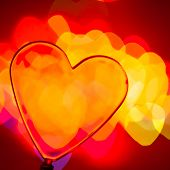 Red transparent plastic heart with blured lights in background, very shallow DOF