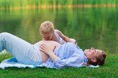 Little boy 2-3 yo kissing his pregnant mother