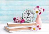 Beautiful flowers in vase on table on light blue background