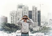 man with binoculars and town background