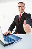 Positive businessman in suit with thumbs up in his office