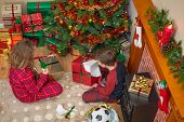 Overhead photo of children, a boy and a girl, sitting by the tree unwrapping their presents on Christmas day.