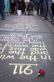 NEW YORK - SEPT 11, 2014: A red rose lays next to the numbers 911 and a phrase written by New York City artist Hans Honchar in colorful chalk on the sidewalk near the World Trade Center in Manhattan.