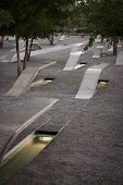 ARLINGTON, VA - SEPT 13, 2014: Granite and stainless steel memorial units and Crape Myrtle trees at the Pentagon Memorial. Each bench has a lit pool of water and name of each victim of the 911 attack.