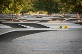 ARLINGTON, VA - SEPT 13, 2014: Flowers left on one of the granite and stainless steel memorial units at the Pentagon Memorial. The benches have the name of each victim of the 2001 attack.