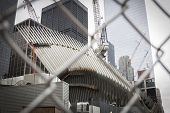 NEW YORK - SEPT 11, 2014: The white spokes of the new Transit Hub still under construction at the World Trade Center site in Lower Manhattan, as seen through the metal safety fence.