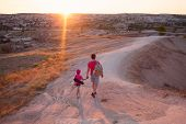 Young Man Father Dad With Little Daughter Kid Child Walking Ain Valley And Meeting Sunset In Cappado