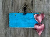 Blank blue sign with red hearts and iron keys hanging on rustic wooden background