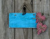 Blank blue wood sign with red hearts and iron keys hanging on rustic wooden background