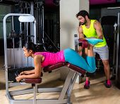 Lying hamstring curl machine girl with personal trainer man