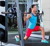 foto of squatting  - girl squats in multipower squatting smith machine barbell at gym smith - JPG