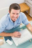 Smiling businessman using his laptop at desk in his office
