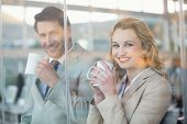 Business people holding cup of coffee through the window at work