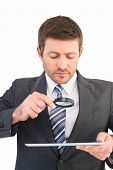 Businessman looking at tablet with magnifying glass on white background