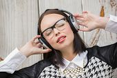 Pretty hipster listening to music against bleached wooden planks