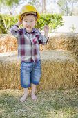 Cute Young Mixed Race Boy Laughing with Hard Hat Outside Near Hay Bale.