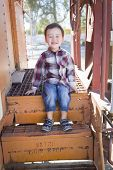 foto of railroad car  - Cute Young Mixed Race Boy Having Fun Outside Sitting on Railroad Car Steps - JPG