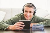 Smiling man listening music and holding cd at home in the living room