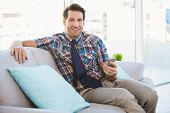 Happy man sitting on the couch sending a text message in bright living room
