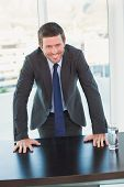 Smiling businessman at his desk in his office