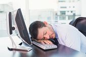 Exhausted businessman sleeping at his desk in his office