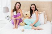 Pretty friends having coffee on bed at home in the bedroom