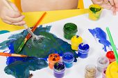 Child Draws Paint On A Sheet