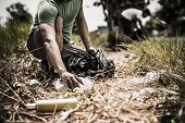 stock photo of crop  - Cropped image of man collecting litter in forest - JPG
