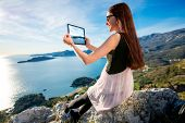 picture of sea-scape  - Young woman in dress photographing with digital table sea scape sitting on the mountain top - JPG
