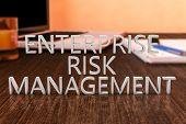 image of enterprise  - Enterprise Risk Management - letters on wooden desk with laptop computer and a notebook. 3d render illustration. ** Note: Shallow depth of field - JPG