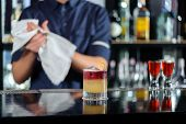 picture of bartender  - Selective focus on beautiful red and yellow cocktail on the counter while bartender drying hands with a towel stands behind the bar counter - JPG