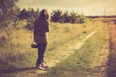 pic of girl walking away  - Girl in sweater walking by rural grassy road in countryside landscape. Photo with vintage mood