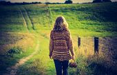 foto of girl walking away  - Girl in sweater walking by rural grassy road in countryside landscape. Photo with vintage mood