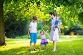 picture of mother baby nature  - Happy family with three kids in a park - JPG