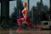 picture of squatting  - Middle Age Woman Performing Dumbbell Squats  - JPG