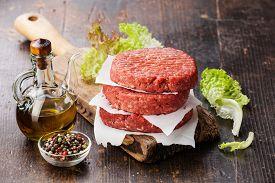 stock photo of burger  - Raw Ground beef meat Burger steak cutlets and seasonings on dark wooden background - JPG