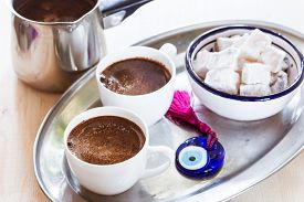 picture of evil  - Cup of coffee on a metal tray with Turkish sweets and glass amulet Evil Eye - JPG