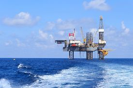 foto of production  - Offshore Jack Up Drilling Rig Over The Production Platform in The Middle of The Sea - JPG