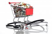 Shopping Cart with pills and capsules and a stethoscope - isolated on a white background