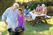 Grandfather and granddaughter preparing barbecue while family having meal in background poster